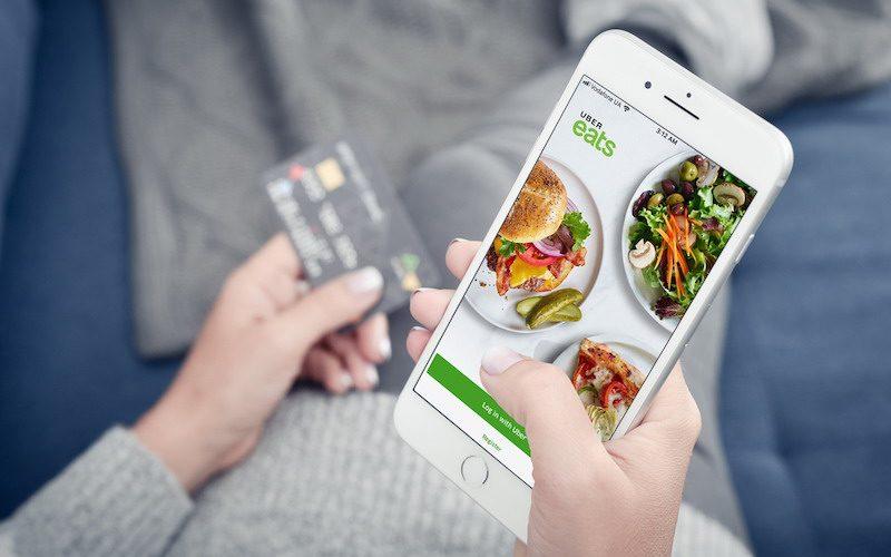 Woman using uber eats app on Apple iPhone 8 plus